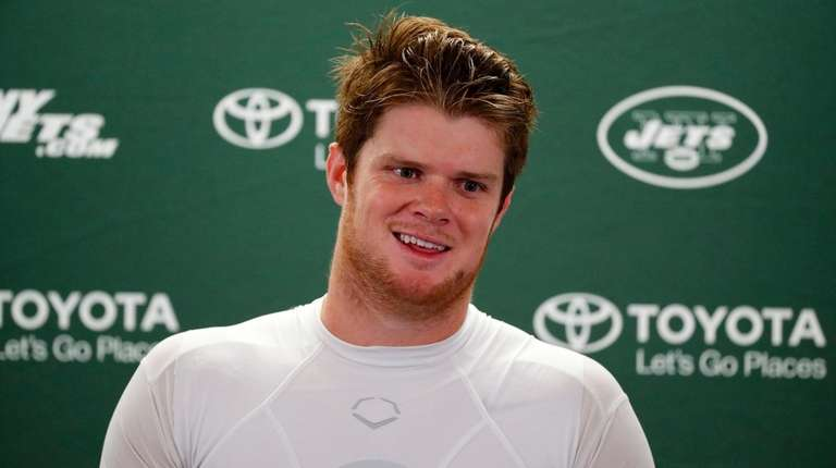 Jets quarterback Sam Darnold smiles while listening to