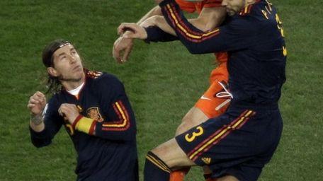 Spain's Sergio Ramos, left, Netherlands' Dirk Kuyt, center,