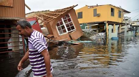 A man walks past destroyed homes in Cataño,