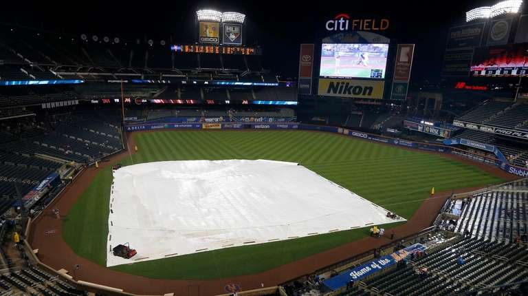 The tarp is seen on the field during