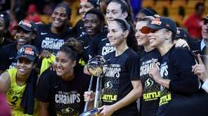 Seattle Storm guard Sue Bird, holding trophy, and
