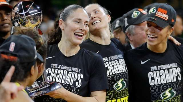 Storm guard Sue Bird, left, holds the championship