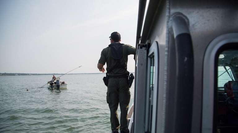 Environmental Conservation Officer Evan Laczi prepares to board