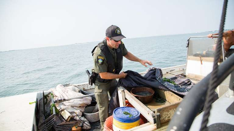 ECO Evan Laczi inspects a clamming boat in