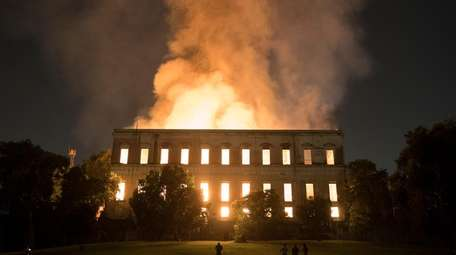 People watch as flames engulf the 200-year-old National