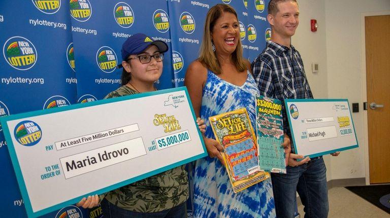 New York Lottery's Yolanda Vega, center, presents checks