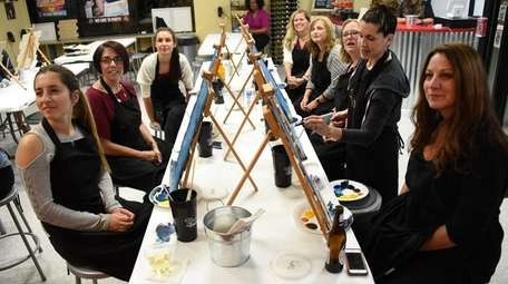 Customers paint and sip during a class at