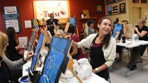 Lindsey Calderone, 26, of Westbury paints during a