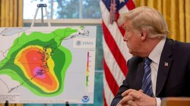 President Donald Trump looks at a map showing