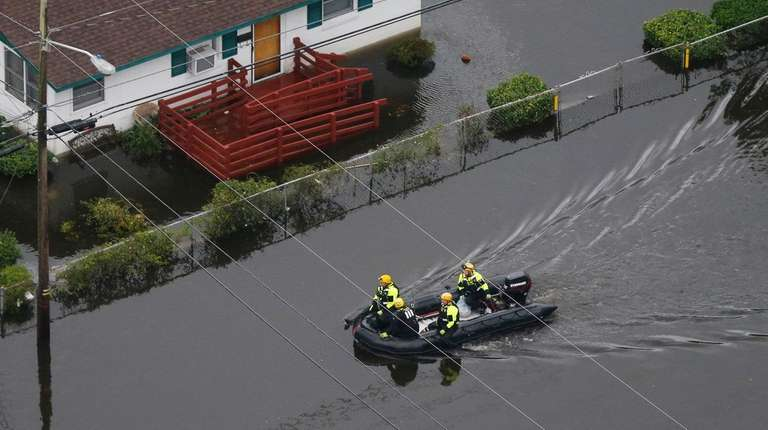 Rescue personnel use a small boat as they