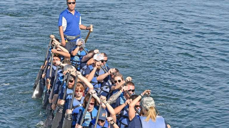 A dragon boat race team paddles to the
