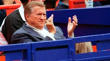 George Steinbrenner claps from the stands while watching