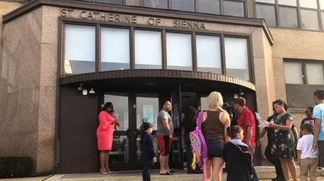 Parents bring their children to St. Catherine of