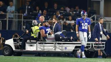 Giants quarterback Eli Manning walks away while teammate