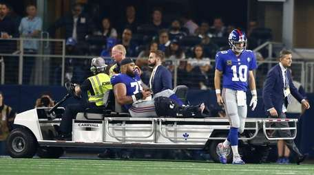 Giants quarterback Eli Manning walks away while teammate