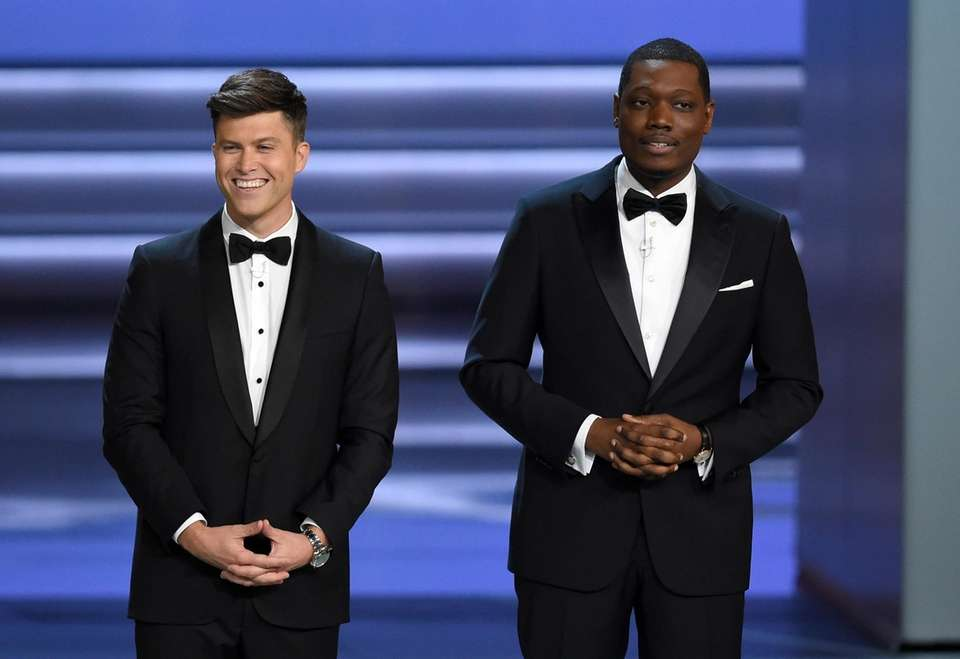 Hosts Colin Jost, left, and Michael Che speak