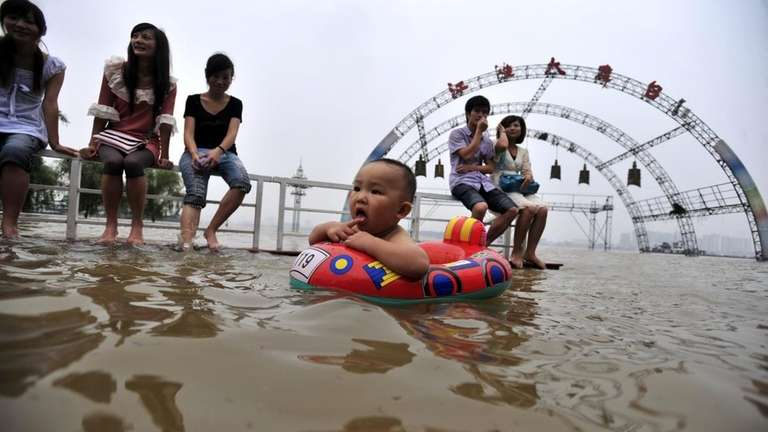 Residents enjoy the water along a flooded riverbank