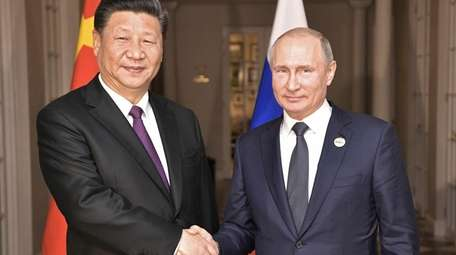 China's President Xi Jinping poses with Russia's President