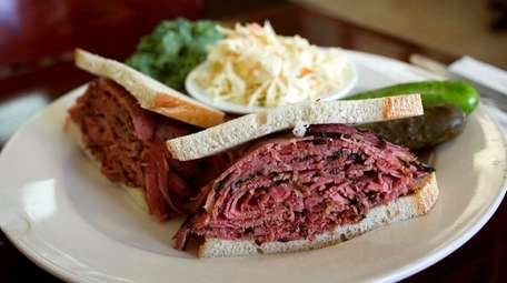 A pastrami sandwich served with pickles and coleslaw