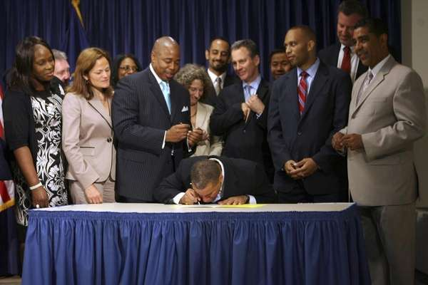 Gov. David Paterson, center, signs a bill prohibiting