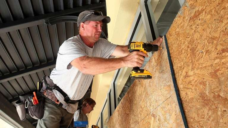 Boarding up windows can help protect a house