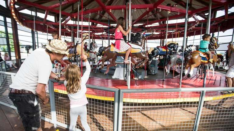 A restored 100-year-old carousel goes round and round