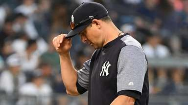 Yankees manager Aaron Boone walks back from the