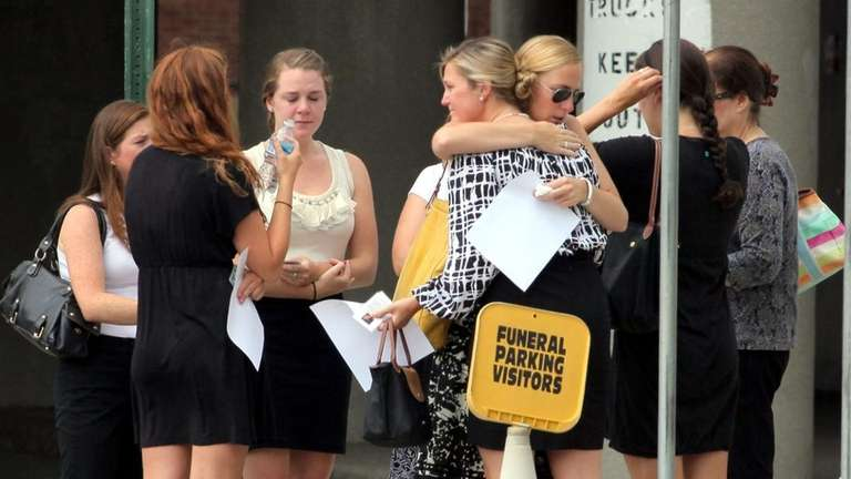 Mourners comfort one another outside of Dalton Funeral