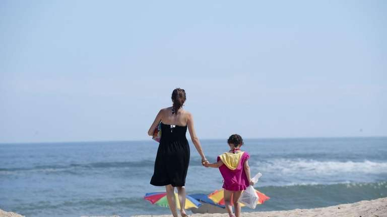 A mother and daughter walk onto Kirk Beach