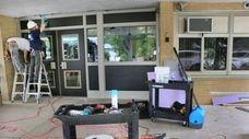 Workers upgrade doorways at Village Elementary School in