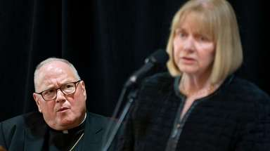 Cardinal Timothy Dolan listens to retired Judge Barbara