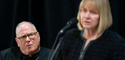 Cardinal Timothy Dolan listens to retired Judge Barbara