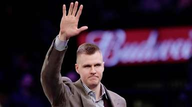 Knicks' Kristaps Porzingis waves to fans before a