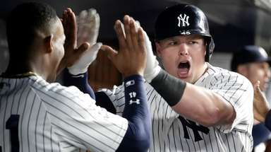 The Yankees' Luke Voit is congratulated by teammates