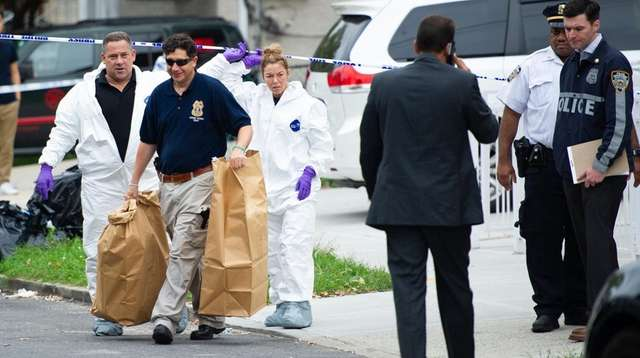Police carry bags of evidence from the residence