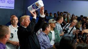 President Donald Trump tosses paper towels into a
