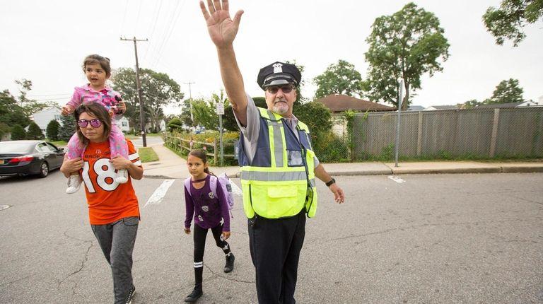 Gerry Perricone helps Ashlei Franzino cross Shore Road