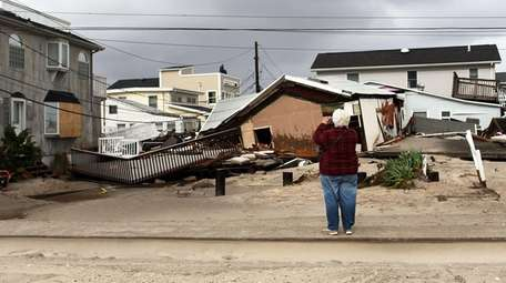 A woman photographs damage after Hurricane Sandy on