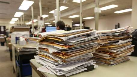 Property tax files are stacked for processing by