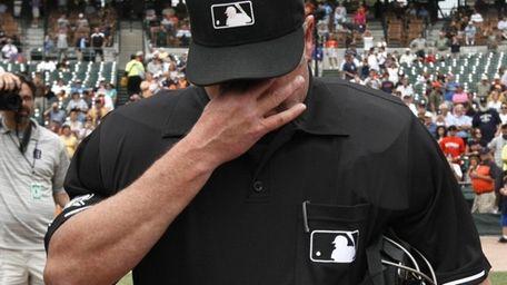 Umpire Jim Joyce wipes tears during the exchange
