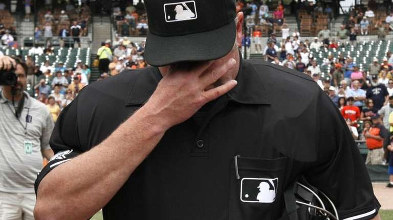 Umpire Jim Joyce wipes tears during the exchange