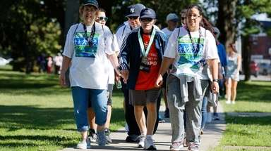 Andrea Irizarry, 70, left, walks with her husband,