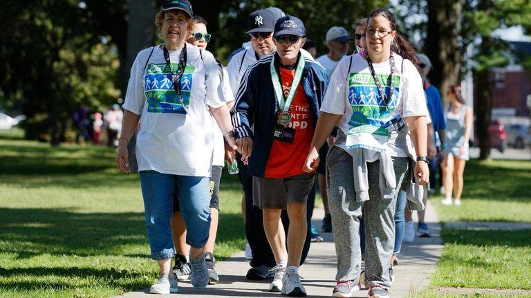 Andrea Irizarry, 70, left, walks with her husband,