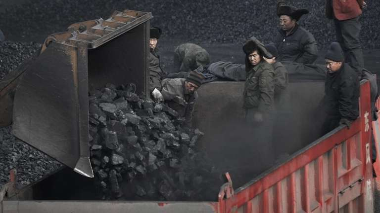 In this file photo, workers load coal into