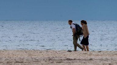 People walk along the shore near Field 6