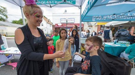 Face painter Tara Scarfo shows Nico Stasio of