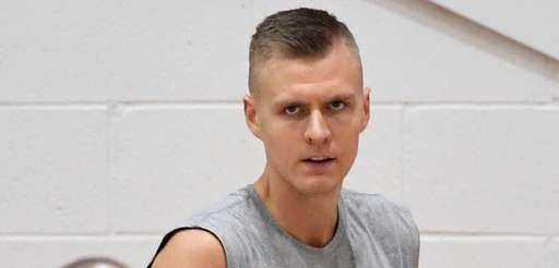 The Knicks' Kristaps Porzingis looks on as coach