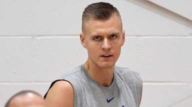 The Knicks' Kristaps Porzingis looks on as coach