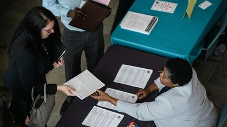 A woman hands over her resume during the