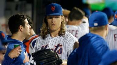 Noah Syndergaard gets congratulated by teammates in the